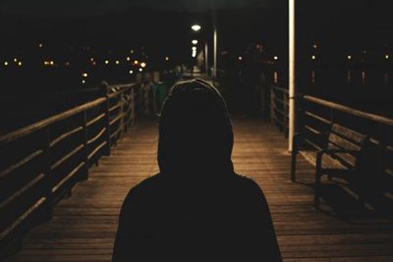 Hombre que está de espaldas cruzando un puente de noche