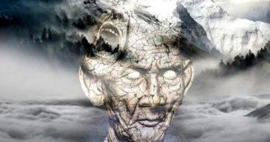 Imagen fantástica de un hombre que parece de piedra y que atrás tiene unas montañas con niebla
