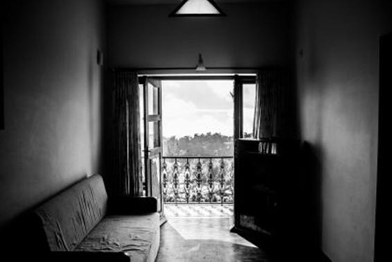 Fotografía en blanco y negro de una habitación con una ventana al fondo abierta a la luz del día