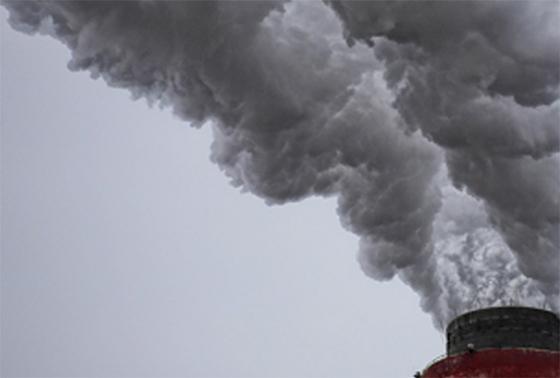 Detalle de una chimenea fábrica con mucho humo