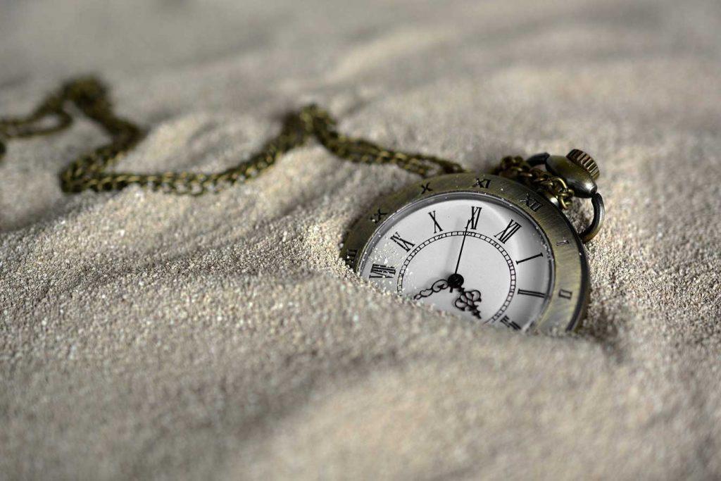 Reloj de arena enterrado en la arena